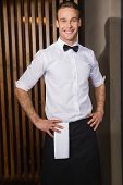Handsome waiter posing and standing hands on hips in a bar