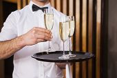 Waiter holding tray of champagne in a bar
