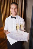 Handsome smiling waiter holding tray of champagne in a bar