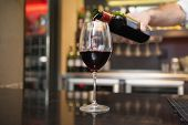 Hand pouring red wine into glass in a bar