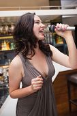 Beautiful young woman singing into a microphone at the nightclub
