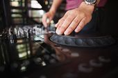 Close up of hands spinning the decks at the nightclub