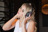 Pretty blonde listening to music with eyes closed at the nightclub