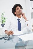 Businessman in shirt writing and thinking in the office