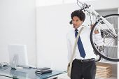 Attractive businessman carrying his bike in his office