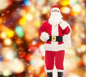christmas, holidays and people concept - man in costume of santa claus with bag over red lights background