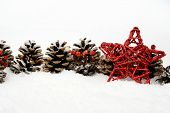 Pine Cones With Red Star On Snow In Line On White