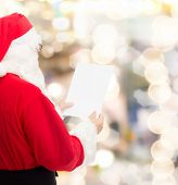 christmas, holidays and people concept - man in costume of santa claus reading letter over lights background