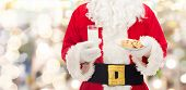 christmas, holidays, food, drink and people concept -close up of santa claus with glass of milk and cookies over lights background