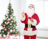 christmas, holidays, gesture and people concept - man in costume of santa claus with notepad pointing finger up over living room and tree background