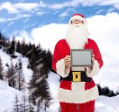 christmas, advertisement, technology, and people concept - man in costume of santa claus with tablet pc computer over snowy mountains background