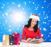 christmas, technology and people concept - smiling woman in santa helper hat with shopping bags and tablet pc computer over blue snowy background