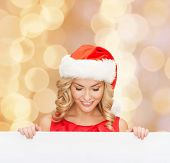 christmas, x-mas, people, advertisement and sale concept - happy woman in santa helper hat with blank white board over beige lights background
