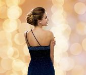 people, holidays and glamour concept - smiling woman in evening dress over beige lights background from back