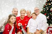 family, holidays, generation, christmas and people concept - smiling family with camera or smartphone and monopod taking selfie at home