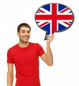 education, fogeign language, english, people and communication concept - smiling young man holding text bubble of british flag