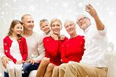 family, holidays, generation, christmas and people concept - smiling family with camera making selfie and sitting on couch at home