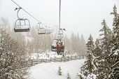 picture of ropeway  - Chairlift with skiers in snowfall at alpine ski resort - JPG