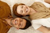 Attractive young couple lying on carpet, looking at camera, smiling happy. Above view.