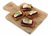 Canape herring with beets on rye toast, on wooden board, isolated on white