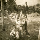 POLAND, CIRCA FIFTIES: Vintage photo of parents with two sons on swing
