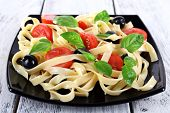 Spaghetti with tomatoes, olives and basil leaves on black plate on wooden background