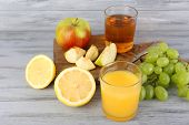glasses of juice with fresh fruits on grey wooden table