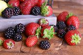 Strawberries and blackberries on tray on wooden background