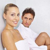 Smiling couple resting in relaxation room in spa after sauna session