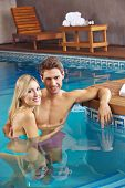 Happy couple bathing in swimming pool of a hotel