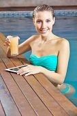 Smiling woman using a tablet computer in a swimming pool in summer
