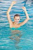 Happy woman bathing in swimming pool in summer in a hotel