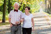 stock photo of stroll  - Aged cheerful marriage and autumn stroll in park - JPG
