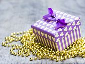 Purple Gift Box With Yellow Hearts Upon Golden Pearls