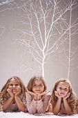 Three calm girls looking at camera while lying in winter forest
