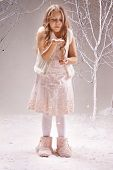 Cute little girl in smart dress playing with snowflakes among bare trees