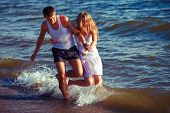 happy couple running on the beach. Sunset time.