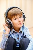 A boy having fun listening to music on headphones.