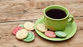 tea cup with colorful cookies, and  brown muffin on table