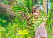 young smiling happy girl having fun in palm trees on natural bac