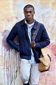 fashionable african hipster man portrait leaning against distressed urban wall background