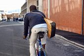 Black african mad riding bicycle in urban city commuting with speed and hipster trendy transportation