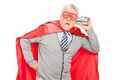 Shocked senior superhero with a tin can phone isolated on white background