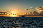 Fiery tropical ocean sunset over a calm blue sea as the glowing orange sun drops below the horizon and low cloud cover