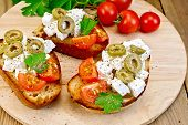 Sandwich with feta and olives on round board