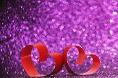 Decorative hearts of red ribbon on shiny glitter background