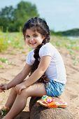 Laughing little girl posing sitting on log