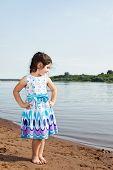 Little girl posing in smart dress on lake backdrop