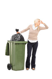 stock photo of disgusting  - Full length portrait of a disgusted woman standing next to a trash can isolated on white background - JPG