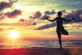 pic of yoga silhouette  - Silhouette of young girl standing at yoga pose on the beach during an amazing sunset - JPG